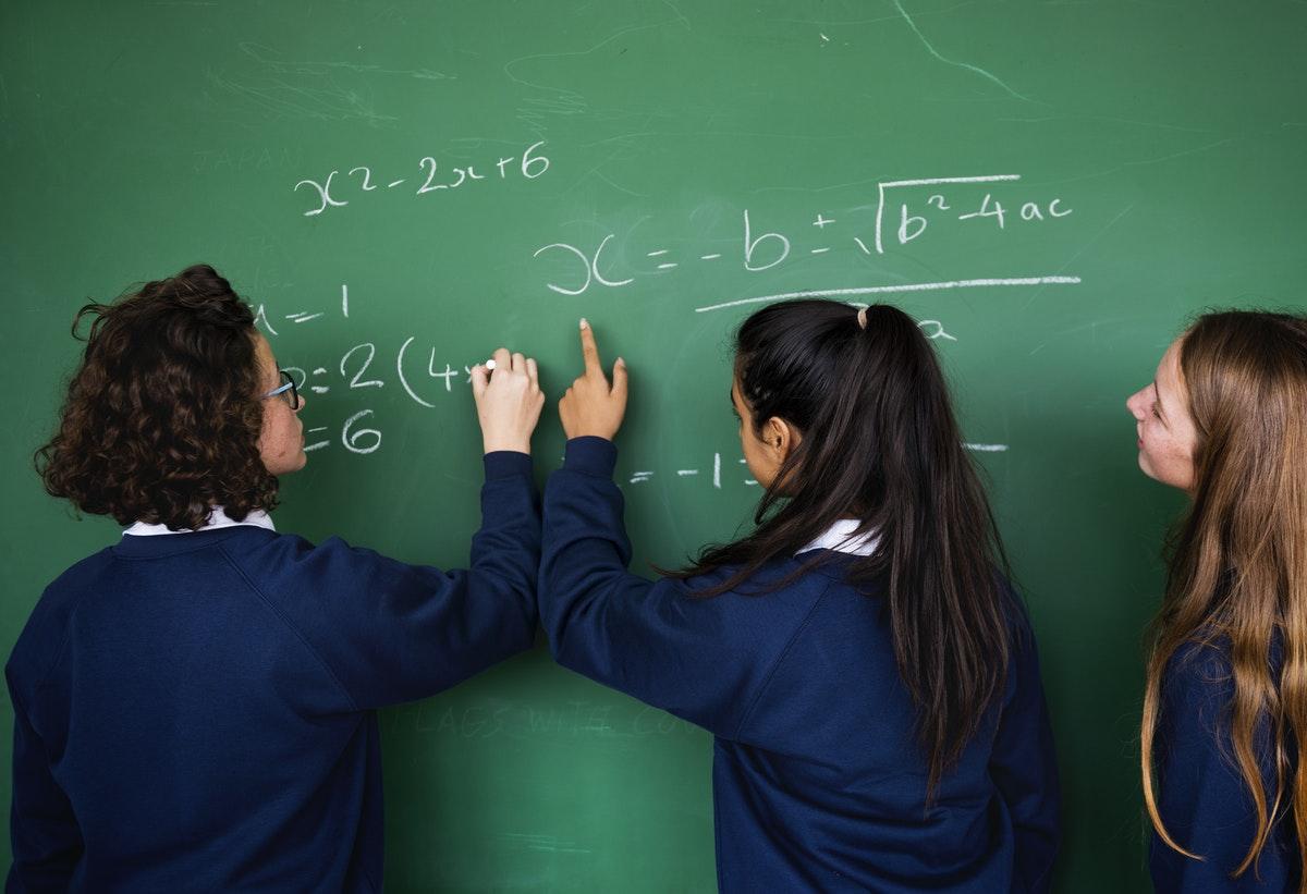 girls writing on a chalk board